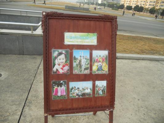 Pyongyangites are exhorted to have souvenir pics taken. Note the little girl pictured posing with her cell phone